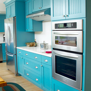 Design ideas for a mid-sized eclectic l-shaped eat-in kitchen in Milwaukee with turquoise cabinets, white splashback, stainless steel appliances, light hardwood floors, with island, a single-bowl sink, flat-panel cabinets, yellow floor and white benchtop.