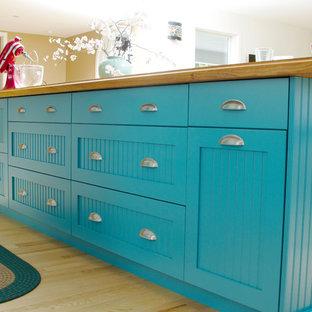 Foto på ett mellanstort eklektiskt gul kök, med blå skåp, träbänkskiva, vitt stänkskydd, rostfria vitvaror, ljust trägolv, en köksö, en enkel diskho, släta luckor och gult golv