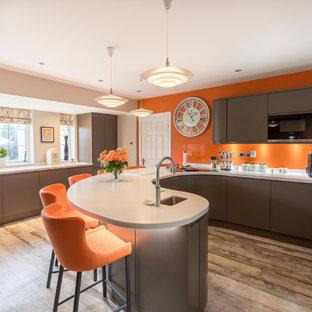 他の地域のコンテンポラリースタイルのおしゃれなキッチン (アンダーカウンターシンク、フラットパネル扉のキャビネット、茶色いキャビネット、オレンジのキッチンパネル、ガラス板のキッチンパネル、茶色い床、白いキッチンカウンター) の写真