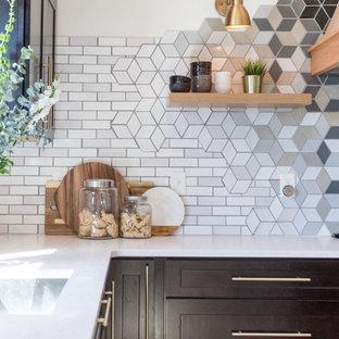 ミネアポリスの大きいコンテンポラリースタイルのおしゃれなキッチン (アンダーカウンターシンク、シェーカースタイル扉のキャビネット、濃色木目調キャビネット、クオーツストーンカウンター、マルチカラーのキッチンパネル、セラミックタイルのキッチンパネル、シルバーの調理設備の、淡色無垢フローリング、茶色い床、白いキッチンカウンター) の写真