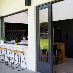 Design ideas for a large modern u-shaped kitchen pantry in Other with a submerged sink, flat-panel cabinets, composite countertops, black splashback, ceramic splashback, black appliances, concrete flooring, an island and white worktops.