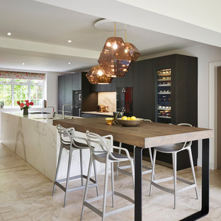This is an example of a contemporary galley kitchen in Cheshire with flat-panel cabinets, dark wood cabinets, black appliances, an island, beige floors and white worktops.