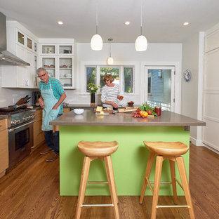 サンフランシスコの中サイズのエクレクティックスタイルのおしゃれなキッチン (アンダーカウンターシンク、フラットパネル扉のキャビネット、淡色木目調キャビネット、クオーツストーンカウンター、白いキッチンパネル、セラミックタイルのキッチンパネル、シルバーの調理設備の、無垢フローリング、茶色い床、グレーのキッチンカウンター) の写真