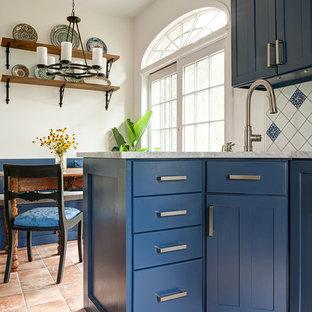 フィラデルフィアの小さい地中海スタイルのおしゃれなキッチン (シングルシンク、シェーカースタイル扉のキャビネット、青いキャビネット、大理石カウンター、青いキッチンパネル、セラミックタイルのキッチンパネル、シルバーの調理設備、テラコッタタイルの床、アイランドなし、オレンジの床) の写真