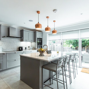 This is an example of a large classic l-shaped kitchen/diner in Surrey with an integrated sink, shaker cabinets, grey cabinets, quartz worktops, white splashback, stone slab splashback, black appliances, white worktops, an island and grey floors.