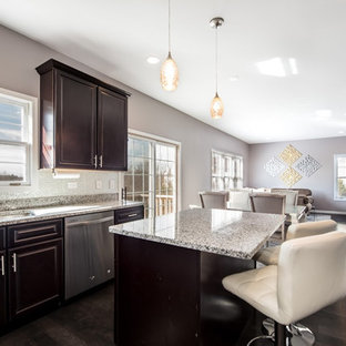 Mid-sized transitional l-shaped open plan kitchen in Chicago with a double-bowl sink, raised-panel cabinets, dark wood cabinets, recycled glass benchtops, stainless steel appliances, dark hardwood floors, with island, brown floor, metallic splashback, glass sheet splashback and grey benchtop.