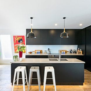 Contemporary kitchen in Melbourne with a double-bowl sink, flat-panel cabinets, black cabinets, white splashback, stainless steel appliances, light hardwood floors and with island.