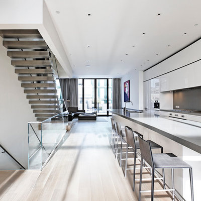 Kitchen - modern galley kitchen idea in New York with flat-panel cabinets, white cabinets, gray backsplash and stainless steel appliances