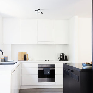 Photo of a contemporary l-shaped kitchen in Sydney with a drop-in sink, flat-panel cabinets, white cabinets, white splashback, glass sheet splashback, black appliances, concrete floors, with island, grey floor and white benchtop.