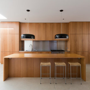 Photo of a mid-sized modern single-wall open plan kitchen in Sydney with medium wood cabinets, wood benchtops, metallic splashback, flat-panel cabinets, concrete floors, stainless steel appliances and with island.