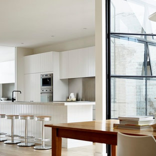 Design ideas for a large scandinavian single-wall open plan kitchen in Sydney with louvered cabinets, white cabinets, limestone benchtops, grey splashback, stainless steel appliances, light hardwood floors, with island, brown floor and white benchtop.