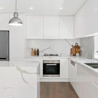 Contemporary l-shaped eat-in kitchen in Sydney with a double-bowl sink, white cabinets, stainless steel appliances, with island, brown floor, flat-panel cabinets, white splashback, stone slab splashback, dark hardwood floors and white benchtop.