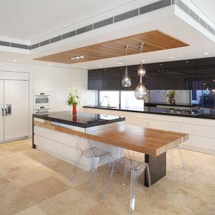 Ejemplo de cocina contemporánea con armarios con paneles lisos, puertas de armario blancas, suelo de travertino, una isla y electrodomésticos con paneles