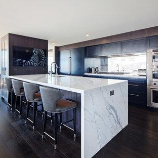 Idee per una grande cucina minimal con lavello sottopiano, ante in stile shaker, ante blu, top in marmo, paraspruzzi a specchio, elettrodomestici in acciaio inossidabile, parquet scuro, isola e pavimento nero