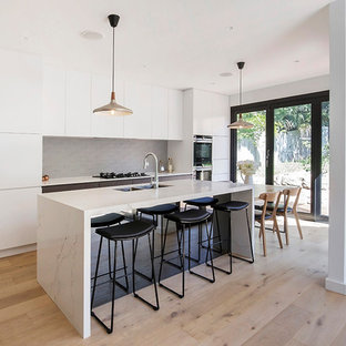 Photo of a contemporary galley eat-in kitchen in Sydney with a double-bowl sink, flat-panel cabinets, white cabinets, grey splashback, stainless steel appliances, light hardwood floors, with island, beige floor and white benchtop.