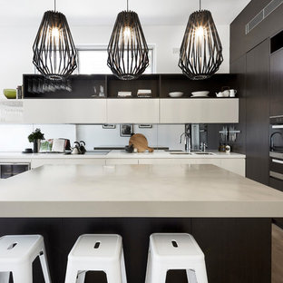 Mid-sized contemporary l-shaped open plan kitchen in Sydney with with island, a double-bowl sink, flat-panel cabinets, dark wood cabinets, mirror splashback, stainless steel appliances and beige benchtop.