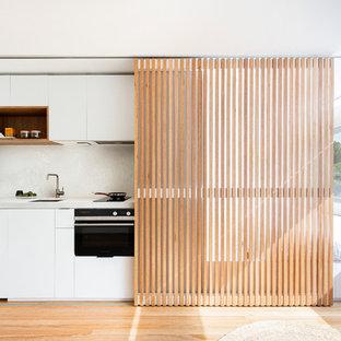 Idées déco pour une petite cuisine ouverte linéaire contemporaine avec un évier encastré, un placard à porte plane, des portes de placard blanches, un électroménager en acier inoxydable, un sol en bois clair, aucun îlot, un sol beige et un plan de travail blanc.