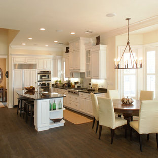 Photo of a tropical eat-in kitchen in Miami with white cabinets, panelled appliances and raised-panel cabinets.