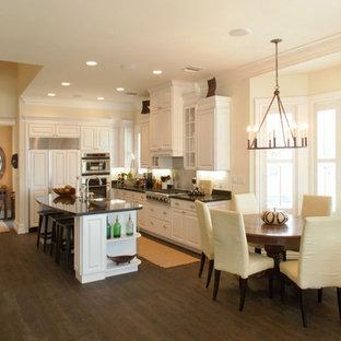 Exemple d'une cuisine américaine exotique avec des portes de placard blanches, un électroménager encastrable et un placard avec porte à panneau surélevé.