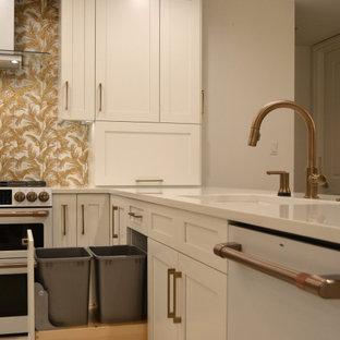 На фото: большая п-образная кухня в стиле современная классика с обеденным столом, врезной раковиной, фасадами в стиле шейкер, белыми фасадами, столешницей из кварцевого агломерата, фартуком цвета металлик, фартуком из керамогранитной плитки, белой техникой, мраморным полом, островом, бежевым полом, белой столешницей и кессонным потолком