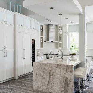 Ispirazione per una cucina a L tradizionale con isola, lavello sottopiano, ante in stile shaker, ante bianche, elettrodomestici in acciaio inossidabile, pavimento grigio e top beige