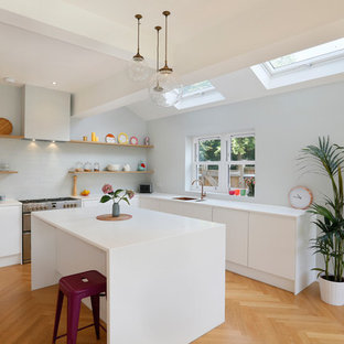 Photo of a contemporary l-shaped kitchen in Other with a submerged sink, flat-panel cabinets, white cabinets, grey splashback, metro tiled splashback, stainless steel appliances, medium hardwood flooring, an island, brown floors and white worktops.