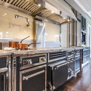 ニューヨークの巨大なエクレクティックスタイルのおしゃれなキッチン (ダブルシンク、フラットパネル扉のキャビネット、青いキャビネット、ステンレスカウンター、ベージュキッチンパネル、ガラス板のキッチンパネル、カラー調理設備、無垢フローリング、茶色い床、グレーのキッチンカウンター) の写真