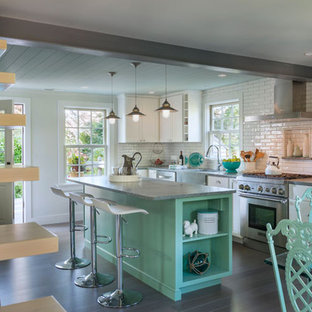 Design ideas for a mid-sized shabby-chic style l-shaped eat-in kitchen in Providence with a farmhouse sink, shaker cabinets, white cabinets, soapstone benchtops, white splashback, subway tile splashback, stainless steel appliances, dark hardwood floors and with island.