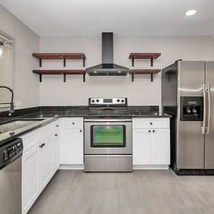 This is an example of a small industrial l-shaped eat-in kitchen in Charlotte with an undermount sink, shaker cabinets, white cabinets, granite benchtops, black splashback, stainless steel appliances, ceramic floors, no island, grey floor and black benchtop.