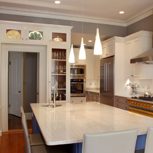 Mid-sized elegant l-shaped medium tone wood floor enclosed kitchen photo in Boston with recessed-panel cabinets, colored appliances, white cabinets, white backsplash, a single-bowl sink, granite countertops, ceramic backsplash and an island