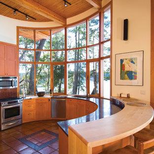 バンクーバーのコンテンポラリースタイルのおしゃれなキッチン (アンダーカウンターシンク、シェーカースタイル扉のキャビネット、中間色木目調キャビネット、赤いキッチンパネル、モザイクタイルのキッチンパネル、シルバーの調理設備の、テラコッタタイルの床、オレンジの床) の写真
