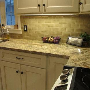 ニューヨークの中サイズのおしゃれなキッチン (アンダーカウンターシンク、落し込みパネル扉のキャビネット、ベージュのキャビネット、御影石カウンター、緑のキッチンパネル、サブウェイタイルのキッチンパネル、シルバーの調理設備の、アイランドなし、マルチカラーのキッチンカウンター) の写真