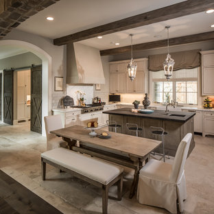 Mid-sized elegant u-shaped limestone floor and beige floor eat-in kitchen photo in Houston with a farmhouse sink, recessed-panel cabinets, stainless steel appliances, white backsplash, limestone backsplash, white cabinets, quartzite countertops and an island