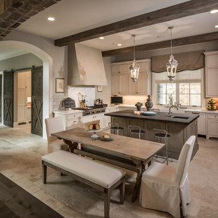Mittelgroße Klassische Wohnküche in U-Form mit Landhausspüle, Schrankfronten mit vertiefter Füllung, Küchengeräten aus Edelstahl, Küchenrückwand in Weiß, Kalk-Rückwand, weißen Schränken, Quarzit-Arbeitsplatte, Kalkstein, Kücheninsel und beigem Boden in Houston
