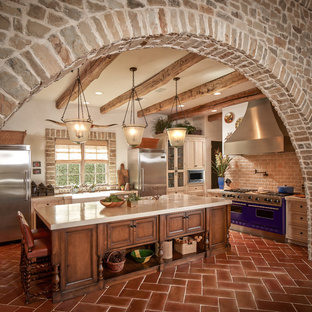 Inspiration for a mediterranean kitchen in Houston with coloured appliances, terra-cotta floors and beige benchtop.
