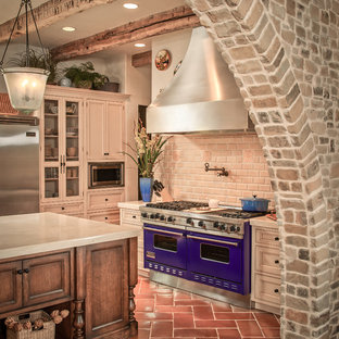 Mediterranean kitchen ideas - Example of a tuscan kitchen design in Houston with subway tile backsplash and colored appliances