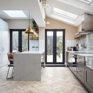 ロンドンの中サイズのトランジショナルスタイルのおしゃれなキッチン (エプロンフロントシンク、グレーのキャビネット、人工大理石カウンター、白いキッチンパネル、セラミックタイルのキッチンパネル、シルバーの調理設備の、セラミックタイルの床、白いキッチンカウンター、シェーカースタイル扉のキャビネット、ピンクの床) の写真