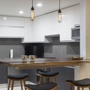 This is an example of a small modern u-shaped eat-in kitchen in Other with a drop-in sink, louvered cabinets, white cabinets, onyx benchtops, grey splashback, stainless steel appliances, marble floors and with island.
