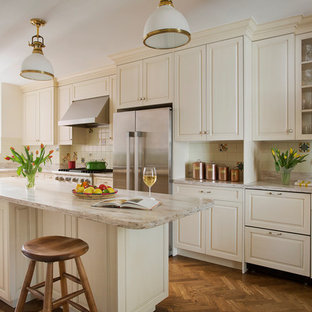 Kitchen - large traditional l-shaped medium tone wood floor kitchen idea in Boston with an undermount sink, raised-panel cabinets, white cabinets, stainless steel appliances, beige backsplash, quartzite countertops, ceramic backsplash and an island