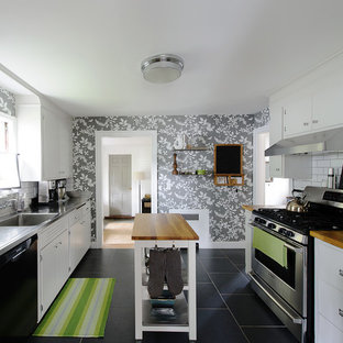 This is an example of a traditional separate kitchen in Boston with an integrated sink, flat-panel cabinets, white cabinets, stainless steel benchtops, white splashback, subway tile splashback and stainless steel appliances.