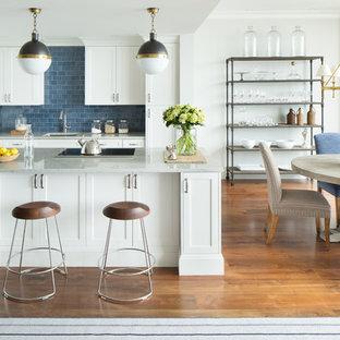 ボストンの大きいトランジショナルスタイルのおしゃれなキッチン (アンダーカウンターシンク、シェーカースタイル扉のキャビネット、白いキャビネット、青いキッチンパネル、サブウェイタイルのキッチンパネル、パネルと同色の調理設備、無垢フローリング) の写真