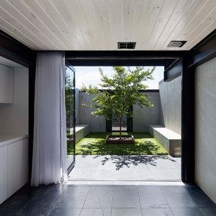 Foto de cocina lineal, minimalista, de tamaño medio, con fregadero bajoencimera, armarios con paneles lisos, puertas de armario blancas y suelo de pizarra