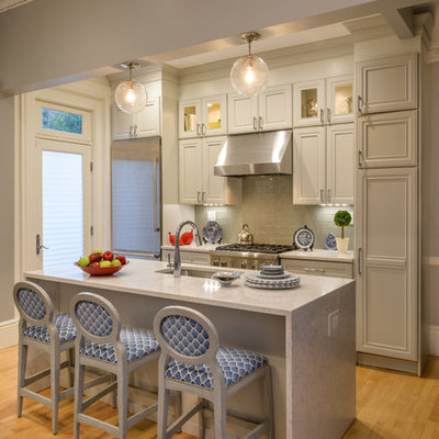 Example of a classic galley medium tone wood floor and brown floor kitchen design in Boston with an undermount sink, recessed-panel cabinets, gray cabinets, gray backsplash, subway tile backsplash, stainless steel appliances, an island and white countertops