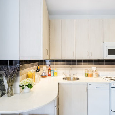 Small trendy l-shaped porcelain tile eat-in kitchen photo in Boston with a drop-in sink, flat-panel cabinets, white cabinets, quartz countertops, white backsplash, ceramic backsplash, white appliances and no island
