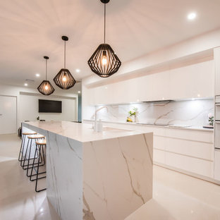 This is an example of a large contemporary galley kitchen in Other with a double-bowl sink, flat-panel cabinets, white cabinets, white splashback, marble splashback, white appliances, beige floor, white benchtop, quartz benchtops and with island.