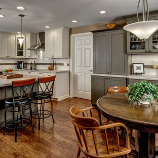 Traditional eat-in kitchen inspiration - Example of a classic u-shaped eat-in kitchen design in Seattle with a drop-in sink, shaker cabinets, white cabinets, laminate countertops, white backsplash, ceramic backsplash and stainless steel appliances