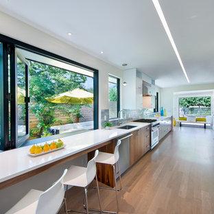 デンバーの中サイズのコンテンポラリースタイルのおしゃれなキッチン (アンダーカウンターシンク、フラットパネル扉のキャビネット、中間色木目調キャビネット、クオーツストーンカウンター、グレーのキッチンパネル、サブウェイタイルのキッチンパネル、シルバーの調理設備の、無垢フローリング、アイランドなし、茶色い床、白いキッチンカウンター) の写真