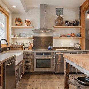 Idéer för funkis kök, med en rustik diskho, skåp i slitet trä, brunt stänkskydd, stänkskydd i metallkakel och rostfria vitvaror
