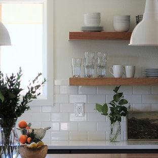 デンバーの大きいインダストリアルスタイルのおしゃれなキッチン (アンダーカウンターシンク、シェーカースタイル扉のキャビネット、グレーのキャビネット、珪岩カウンター、白いキッチンパネル、サブウェイタイルのキッチンパネル、シルバーの調理設備の、淡色無垢フローリング、茶色い床、白いキッチンカウンター) の写真