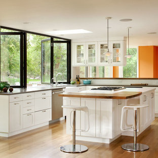 Elegant kitchen photo in Denver with wood countertops, shaker cabinets, white cabinets, white backsplash and stainless steel appliances